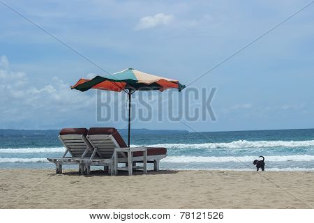 parasol umbrella and chairs on beach with blue ocean behind