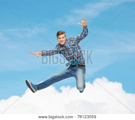 happiness, freedom, movement and people concept - smiling young man jumping in air over blue sky with white cloud background