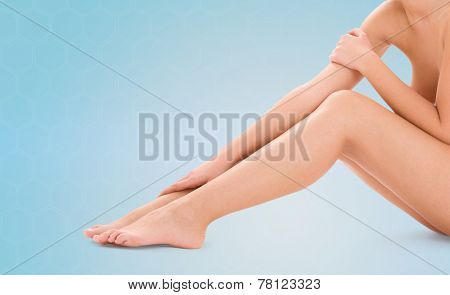 healthcare, beauty and people concept - beautiful woman touching her bare legs over blue background