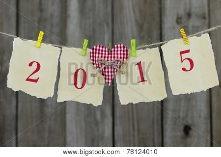 Year 2015 on antique parchment paper hanging on clothesline with red heart by wooden background