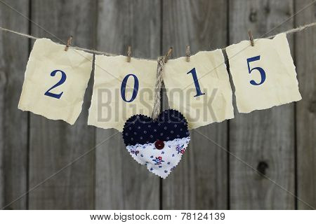 Year 2015 in blue on antique parchment paper hanging on clothesline with heart by wooden background