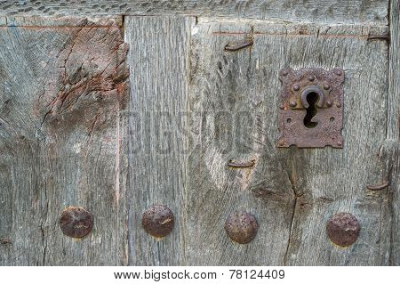 Old run-down wooden door and iron lock