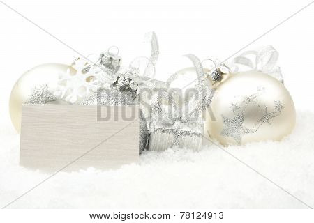 Silver Christmas Decoration On Snow With Wishes Card In Line