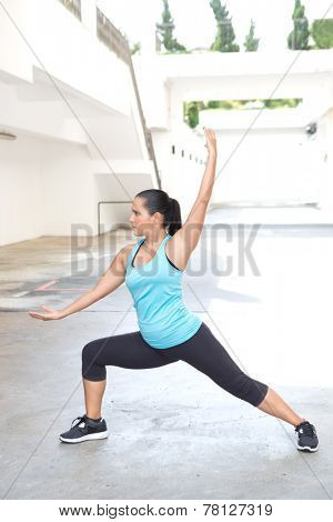 Beautiful hispanic sport woman demonstrating tai chi pose, outdoor. Concept of healthy lifestyle.