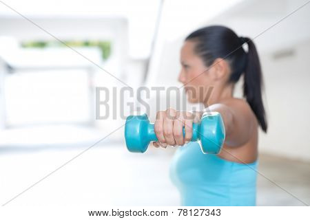 Closeup of woman's hand holding blue dumbbell for her arm training, outdoor.