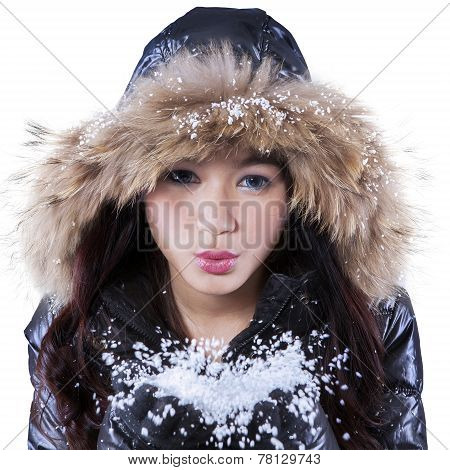Young Girl Blowing Cold Snow