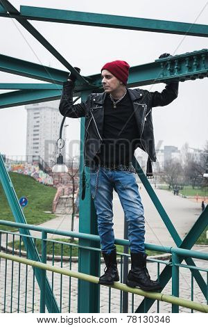 Punk Guy Standing On A Bridge