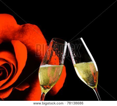 Champagne Flutes With Golden Bubbles On Rose Flowers And Black Background