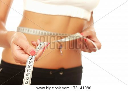 A young woman measuring her waist isolated on white background