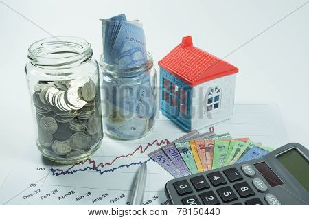 Coins, Jar And House In The Background