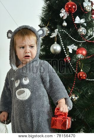 resentful boy near new-year tree