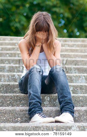 Sad teenage girl sitting alone on the stairs