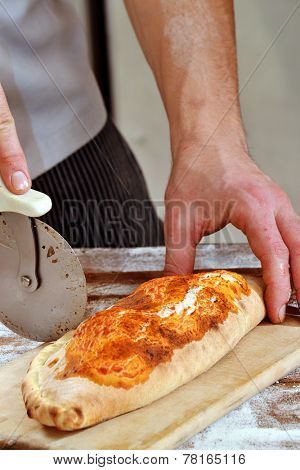 Cutting  and preparing calzone, cooking Italian pizza.