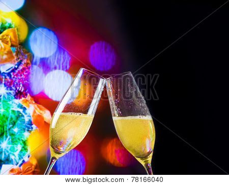 Champagne Flutes With Golden Bubbles On Christmas Lights Bokeh Decoration Background