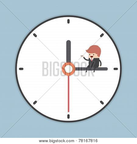 Businessman Sitting On Minute Hand Of Clock With A Cup Of Coffee