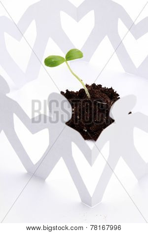 Paper people around a plant, isolated on white