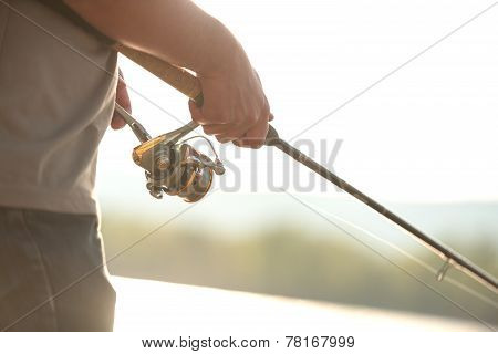 Modern clean fishing rod in hands