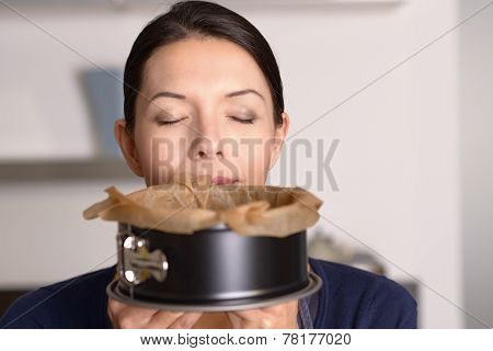 Attractive Woman Enjoying Aroma Of Freshly Baked Cake