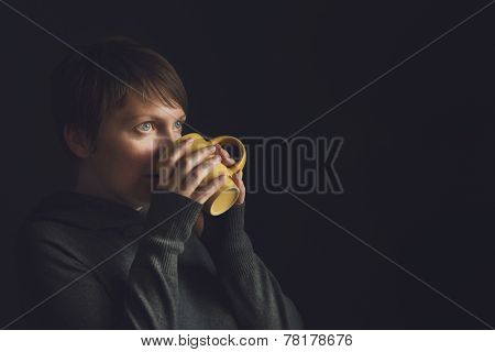 Beautiful Woman Drinking Tea In Dark Room