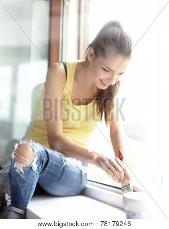 Woman with a paintbrush carefully finishing off around a window frame