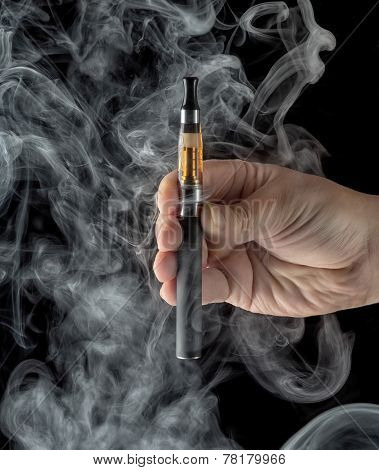 Hand Holding An Electronic Cigarette Over A Dark Background