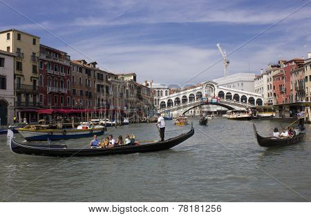 People Sailing on gondolas with Rialto Bridge on the Background