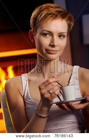 Pretty young woman sitting in cosy room, drinking coffee, thinking.