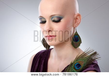 Portrait of beautiful hairless woman using peacock plumes as accessory.