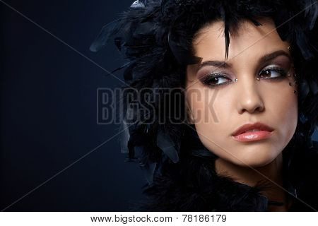 Mystical look of beauty covered in black feather boa, wearing makeup with strasses.