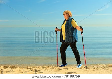 Active Woman Senior Nordic Walking On A Beach