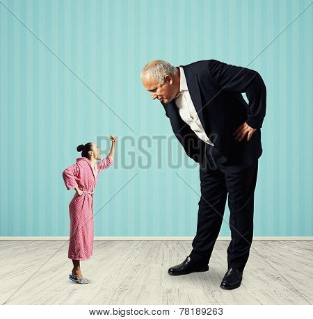 small angry woman screaming at big senior man in black suit