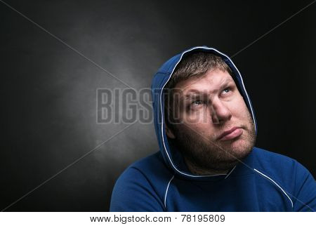Adult man in the hood sits thinking