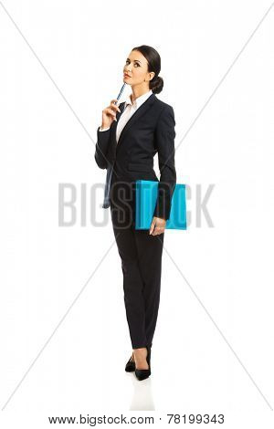 Full length thoughtful businesswoman holding a pen.