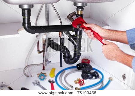 Plumber hands with a wrench. Plumbing renovation background.
