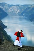 picture of parachute  - Man jumping off a cliff with a parachute - JPG