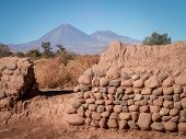 pic of conic  - A conical mountain shot through a gap in a wall San Pedro Chile - JPG