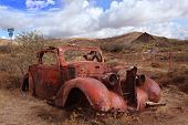 stock photo of bluff  - Old antique car rusting in Arizona Desert with Barn in background - JPG