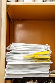 stock photo of stelles  - Stell office bookcase with stack of paper - JPG