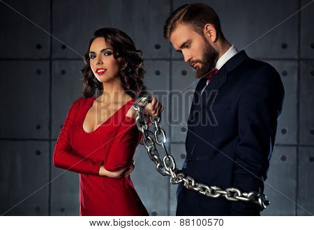 Young happy woman catching man and holding him on heavy chain. Elegant evening clothing.