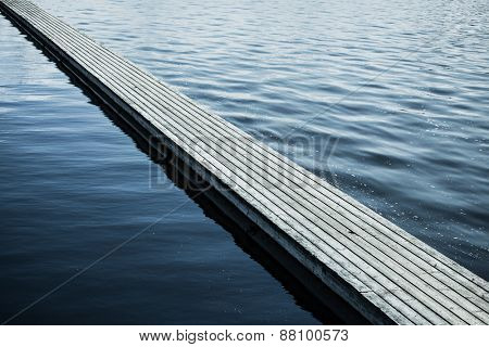 Long floating wooden bridge on water surface. Diagonal composition.