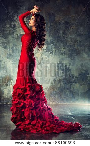 Young slim sexy fashion woman in long red dress standing on stone wall background
