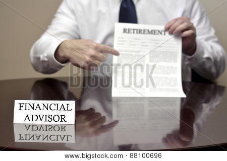 Financial advisor sitting at desk holding Retirement document