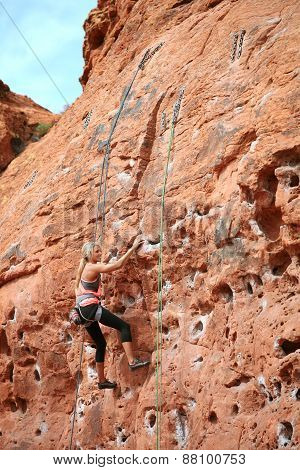 Determined woman rock climbing