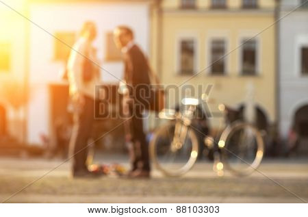 Blurred Couple with bicicle stay on the street at sunny day.