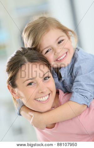 Portrait of cheerful mommy with little girl on shoulders