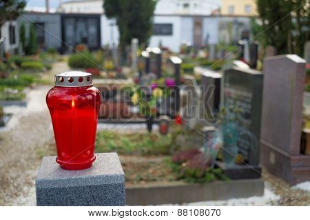 a red lantern lights up in front of graves in a cemetery