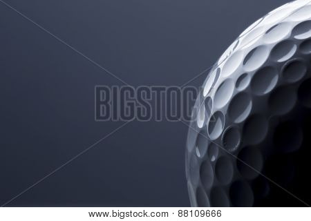 Close up of golf ball isolated on dark blue background, copy space for text.