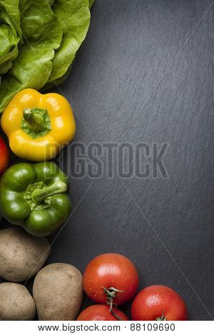 Composition of colorful mixed vegetables isolated on a grey stone background.