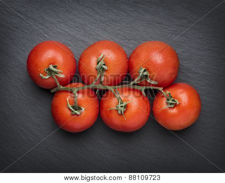 Bunch of fresh tomatoes isolated on dark grey stone slab background.
