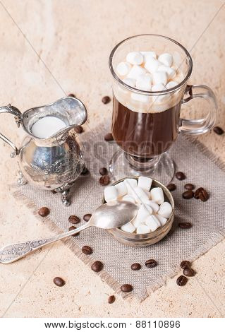 Glass Cup Of Coffee With Marshmallow, Milk Jug And Coffee Beans
